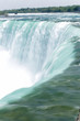 The bright blue water of Niagara Falls flows down the river and over the waterfall in spring