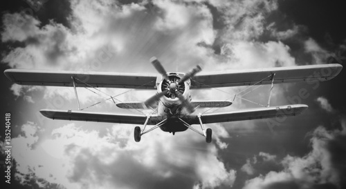 Biplane landing with cloudy sky on the background. Black and whi