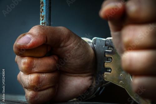 Human hand of prisoner on steel lattice close up. Poster
