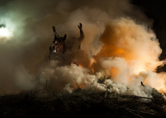 Horses jumping above the fire without fear