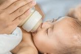 hand of mother feeding milk from bottle and baby sleeping