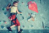 Fototapety little girl climbing a rock wall indoor