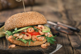 Burger with grilled shrimp, arugula and avocado on wooden board