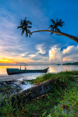 The abandoned boat lies under the coconut trees with beautiful blue sky and white cloud at Gertak Sanggul beach, Pulau Pinang beach during sunrise