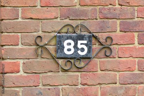 Poster House number 85 sign on wall