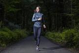 Läuferin in dunklem Wald