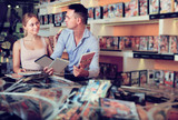 Cheerful family couple selecting erotic video in discount