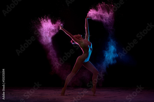 Obraz Fotograficzny Slender girl dancing in color powder cloud