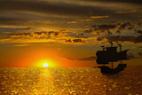 seascape with a golden setting sun and the silhouette of a sailboat