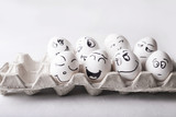 Fototapety Eggs with funny faces in the package on a white background. Easter Concept Photo. Eggs. Faces on the eggs Eggs