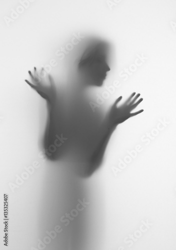 Woman silhouette of face and hands behind a diffuse surface