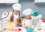 two little girls in chef uniform with ingredients on table