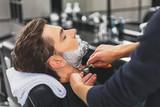 Fototapety Skillful hairdresser using blade for shaving beard