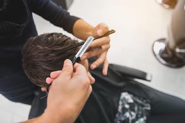 Professional barber serving man in salon