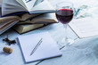 Glass of red wine and a book on a white wooden background