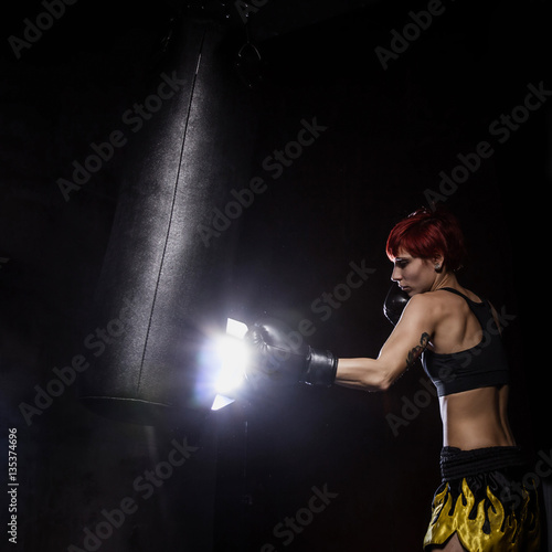 Poster Athlete boxer woman punching a punching bag with dramatic lighting in a dark stu