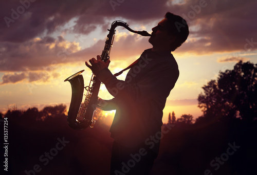 Poster Saxophonist playing sax against sunset
