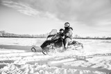 A father and his toddler daughter riding across a snow covered field in a black and white winter landscape