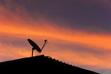 Skyscape in evening with silhouette roof and satellite dish.