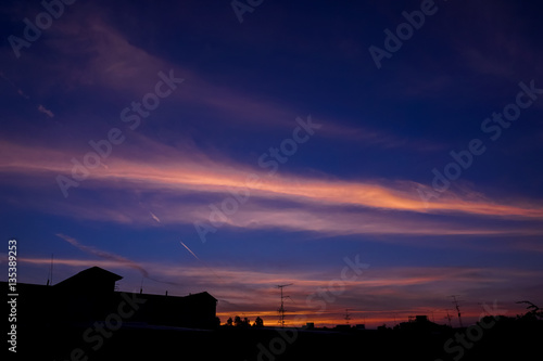 Poster Skyscape in evening with silhouette roof and  satellite dish.