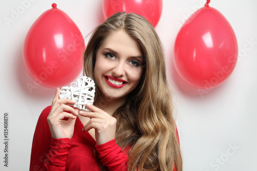Poster Beautiful girl holding white decorative hearta box of gifton Valentine's Day