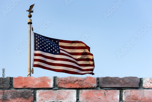 Poster American flag and defocused brick fence, the United States confrontation and ref