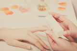 Preparing nails before manicure, beautician file nails