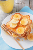 Fresh homemade crispy toast with honey and bananas on white wooden table. Delicious breakfast. close up, selective focus, top view