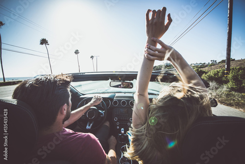 Couple driving on a convertible car Poster