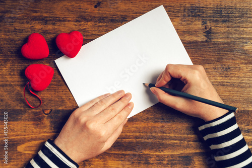 Woman writing love letter for Valentines day