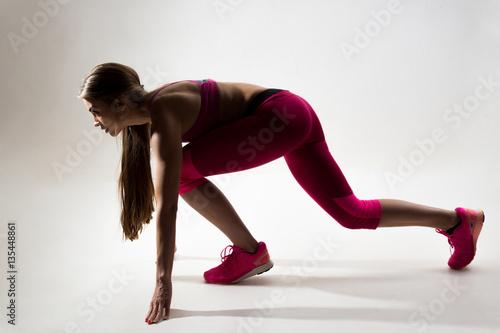 Valokuva A woman dressed in sportswear prepared to run. Studio. White bac
