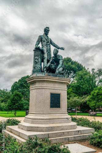 The bronze statue features President Lincoln standing with his left arm out-stretched over a crouching freed slave Tableau sur Toile