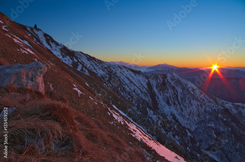 Valokuva Sunrise on the Italian Alps during the winter with a bit of snow covering the dr