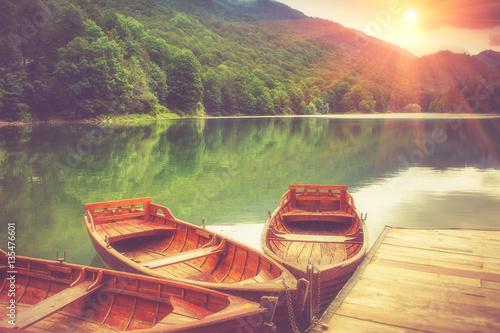 Fototapeta View of glacial mountain Lake Biogradsko, wooden pier and boats in forest. Biogradska Gora National Park. Montenegro. Filtered image:cross processed vintage effect.
