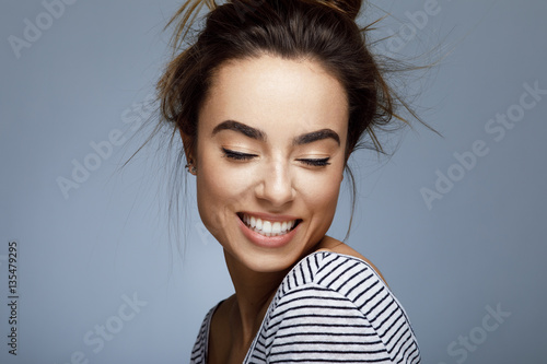 Closeup portrait of young woman with toothy smile in studio