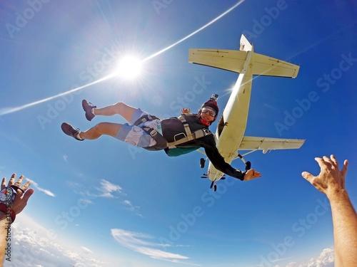 Zdjęcia na płótnie, fototapety, obrazy : Funny parachutist jumps from an airplane on a summer day. Point of view