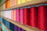 półka z kolorowymi nićmi do szycia