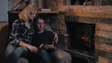 Young Couple Sitting On Sofa Near Fireplace At Winter Season At Home, Man Using Tablet PC