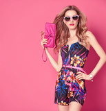 Fashion woman in Trendy Spring Summer Dress. Stylish wavy hairstyle, fashion Sunglasses, Summer Floral Outfit. Glamour Blond lady in Sexy Jumpsuit, fashion pose. Playful Girl,Luxury summer Pink Clutch - 135556832