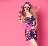 Fashion woman in Trendy Spring Summer Dress. Stylish wavy hairstyle, fashion Sunglasses, Summer Floral Outfit. Glamour Blond lady in Sexy Jumpsuit, fashion pose. Playful Girl,Luxury summer Pink Clutch - 135557037