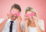 Couple holding hearts over eyes