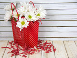 white daisy bouquet in red polka dot gift bag on wood