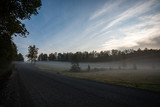 misty countryside landscape with asphalt wavy road in latvia
