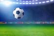Soccer ball, bright spotlight illuminates green football field