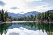 Trees and snow capped mountains reflected in lake in Dixie National Forest, Utah.