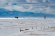 Pier and lighthouse in Lake Michigan during winter with a snow fence in the foreground.