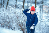 Cute little boy having fun with snowball fight winter