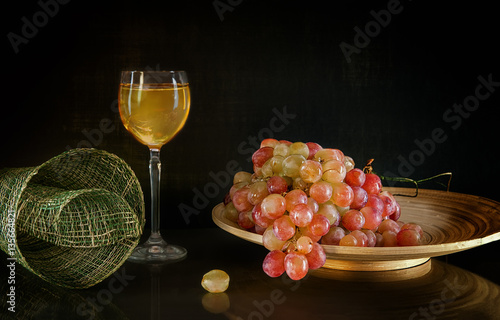 Poster A bunch of grapes lying on a round wooden plate next to a glass of white wine st