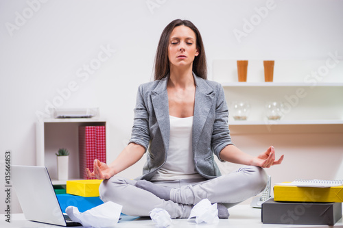 Naklejka Young businesswoman is meditating in her office.