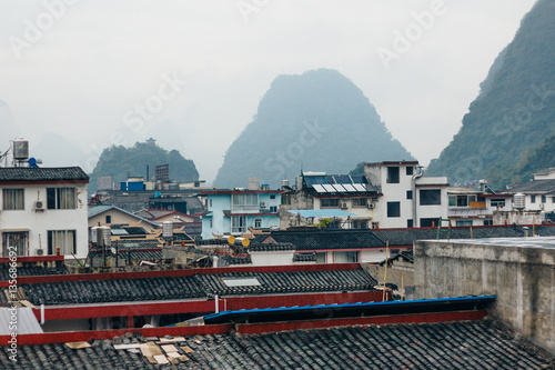 The foggy view of the cityscape and karst rock mountains in Yangshuo, Guilin region, Guangxi Province, China.